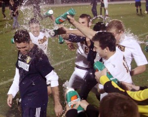 (Left to right) Jason Collister, Noah Keene, Kyle Lester, and Brett Wilkosz douse their coach Chad Ebright with water after the win. Ebright has been the only boys soccer coach in Warrior history.